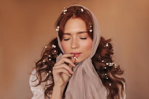 Piękna ciemnowłosa kobieta gryzie biały kwiat. kobieta w chustce pozowanie na na białym tle.