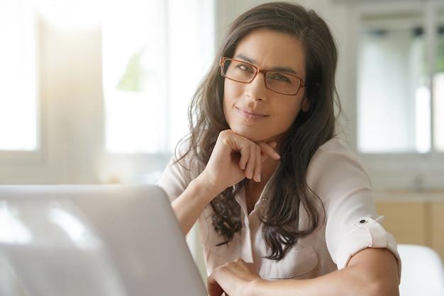 Piękna ciemnowłosa kobieta pracuje w okularach na laptopie