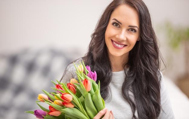 Piękna ciemnowłosa kobieta trzyma w rękach piękny bukiet pełen tulipanów podczas narodowego dnia kobiet.