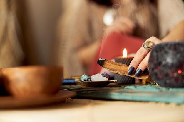 Piękna ciemnowłosa kobieta w szamańskim stroju etnicznym w urządzonym pokoju w stylu bali