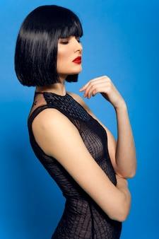 Piękna ciemnowłosa kobieta z fryzurą bob, na niebieskim tle.