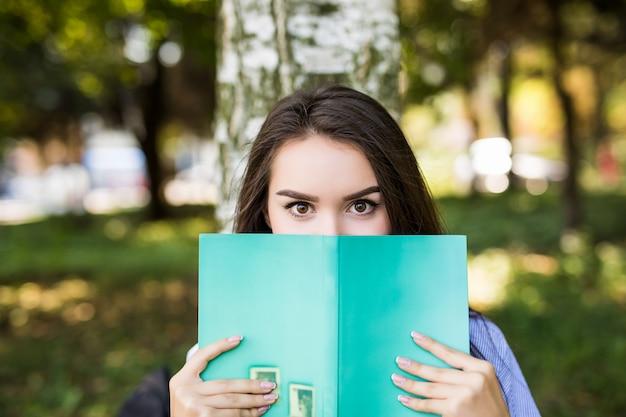 Piękna ciemnowłosa poważna dziewczyna w dżinsowej kurtce zakrywa twarz książką przed letnim zielonym parkiem.