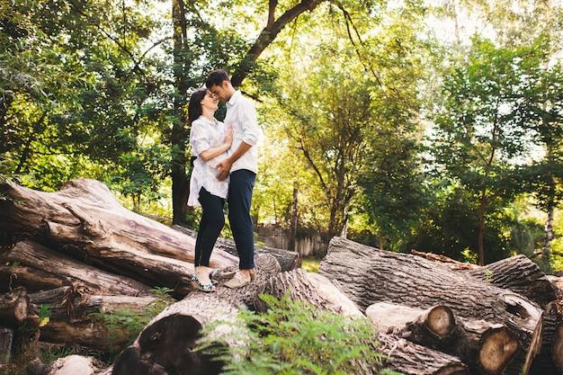 Piękna ciężarna para relaksuje outside w lesie