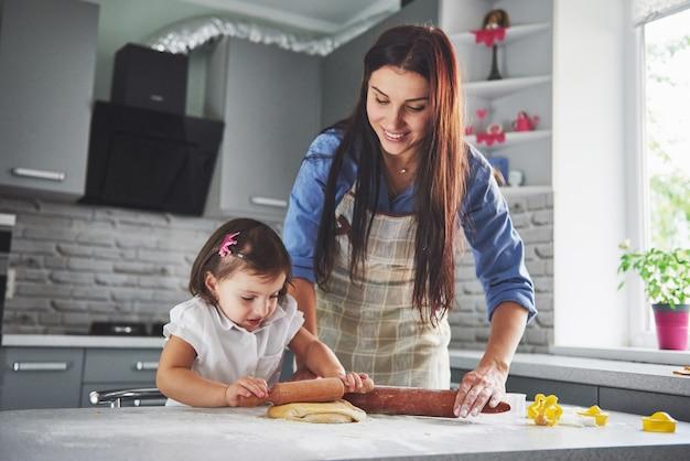 Piękna córka z matką gotującą w kuchni