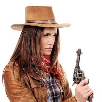Piękna cowgirl z pistoletem na białym tle