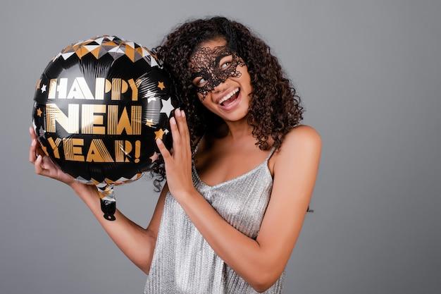 Piękna czarna dziewczyna z balonem szczęśliwego nowego roku na sobie maskę maskującą na białym tle nad szarym