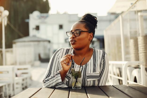 Piękna czarna dziewczyny pozycja w lato parku