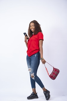 Piękna czarna kobieta uśmiecha się i trzyma telefon