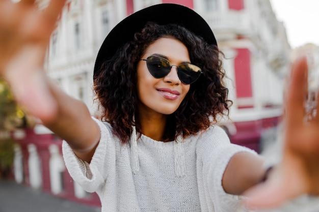 Piękna czarna kobieta ze stylowymi włosami afro dokonywanie autoportret.