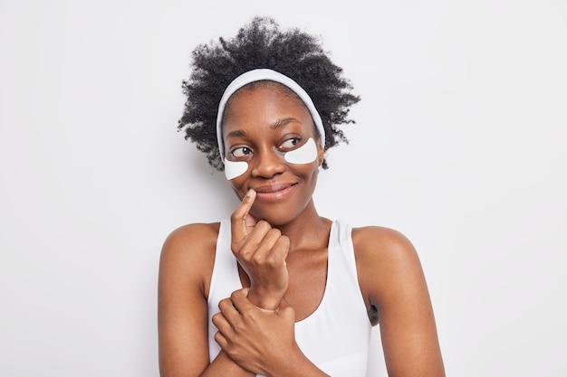 Piękna czarna młoda kobieta ma marzycielski zadowolony wyraz twarzy odwraca wzrok, trzyma palec w pobliżu kącika ust, nakłada łaty na cienie pod oczami