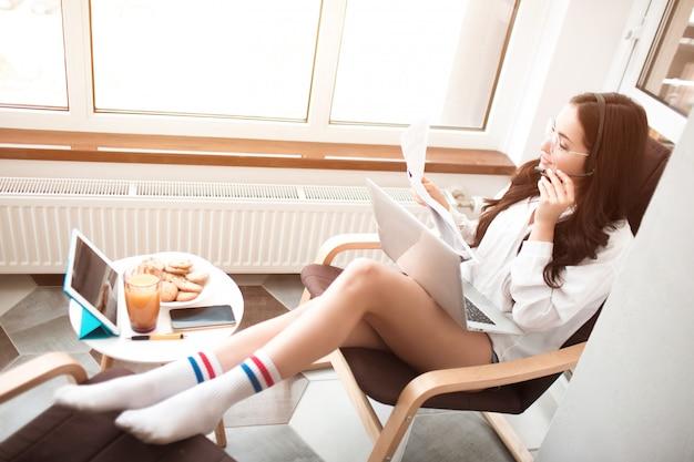 Piękna czarnowłosa kobieta pracuje z domu i używa słuchawek z zestawem słuchawkowym.