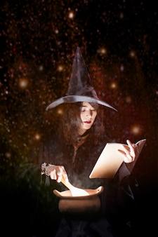 Piękna czarownica azjatyckie dziewczyny gotują eliksir świecące w garnku.