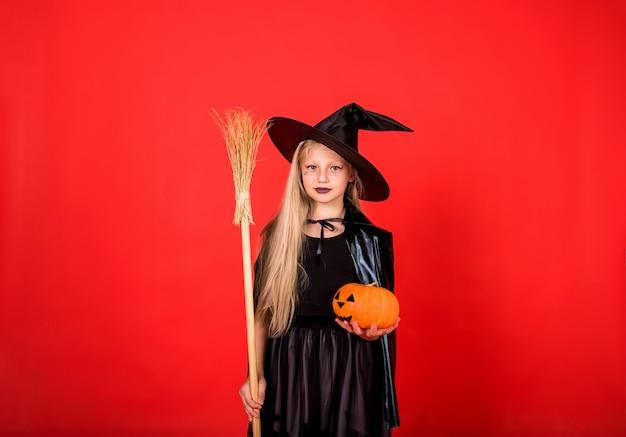 Piękna czarownica dziewczyna w kapeluszu z miotłą i dynią na czerwonej ścianie na białym tle z miejscem na tekst