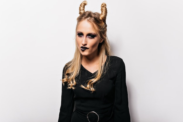 Piękna czarownica z zabawną fryzurą, pozowanie na białej ścianie. zainspirowana blondynka w kostiumie na halloween