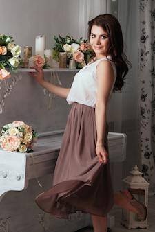 Piękna czarująca brunetka w domu przy starym fortepianie