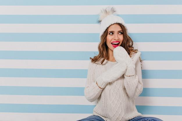 Piękna, czarująca młoda kobieta wygląda przebiegle w lewo i robi zdziwiony wyraz twarzy. portret na odosobnionej ścianie biało-niebieskiej