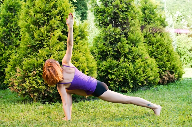 Piękna czerwona kobieta robi fitness lub ćwiczeń jogi