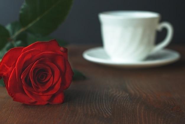 Piękna czerwona róża i biała filiżanka gorącej herbaty lub kawy na drewnianym tle