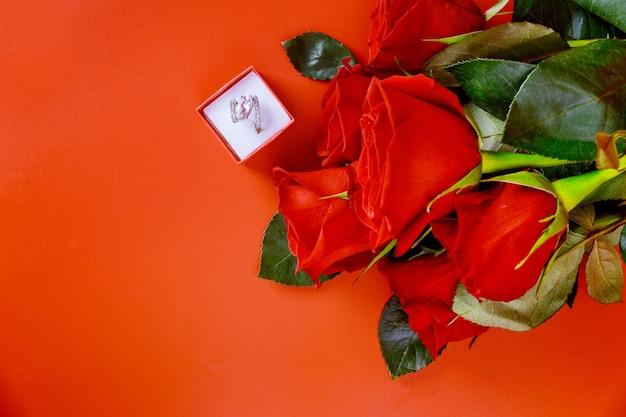 Piękna czerwona róża i pierścionek zaręczynowy. propozycja małżeństwa