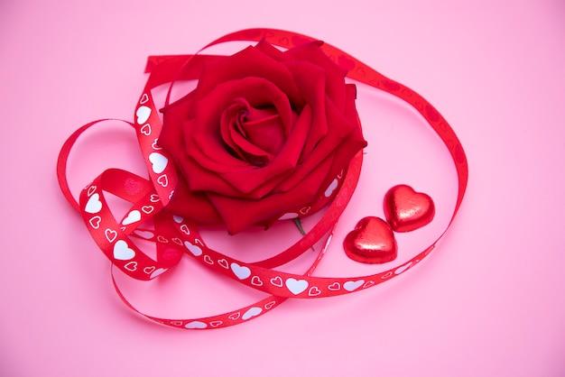 Piękna czerwona róża ze wstążką w czerwone i białe serca