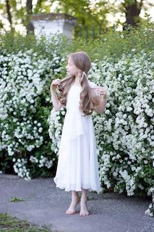 Piękna czuła dziewczyna w wieku 8 lat w białej jedwabnej sukience stoi boso w pobliżu kwitnących białych krzewów, odwraca wzrok