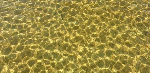Piękna czysta woda z lekkimi zmarszczkami i piaszczystym jeziorem widocznym z dna w słoneczny gorący letni dzień