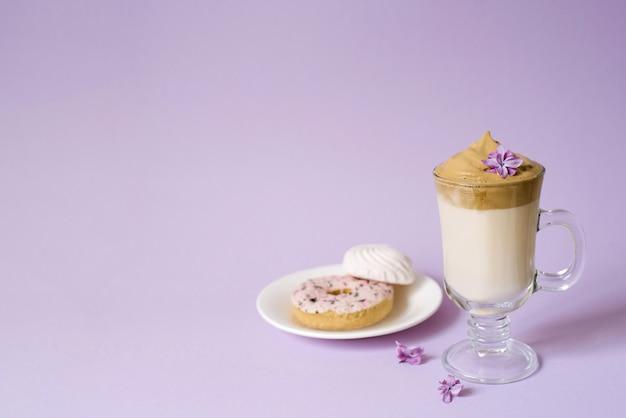 Piękna dalgona pije piankową kawę w przezroczystym kubku i kwiaty bzu na fioletowym tle.