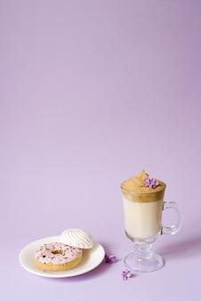 Piękna dalgona pije spienioną kawę w przezroczystym kubku i kwiaty bzu na fioletowym tle. słodycze na talerzu: donat i delikatne pianki. skopiuj miejsce
