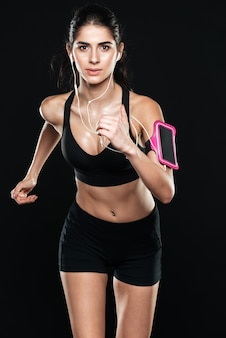 Piękna dama fitness w siłowni biegnącą po czarnej ścianie. spójrz na przód