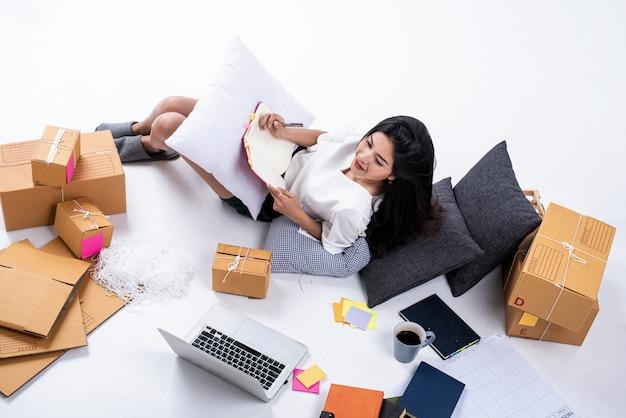 Piękna dama leżąca obok skrzynki pocztowej, używając laptopa i książki do rejestrowania danych sprzedaży online, pakowania do wysłania, pracy w domu, e-commerce, efekt flary