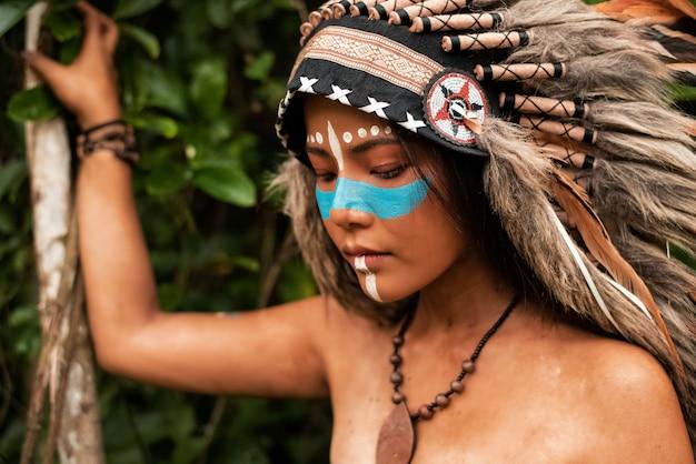 Piękna dama pomalowała twarz i ciało brązowym, jasnoniebieskim kolorem, uniesiona ręka dotknęła jej szyi, portret modelki pozuje, rozmazane światło