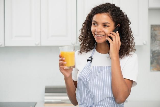 Piękna dama rozmawia przez telefon i trzyma szklankę soku