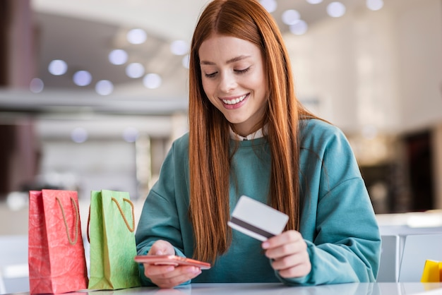Piękna dama trzyma telefon i kartę kredytową