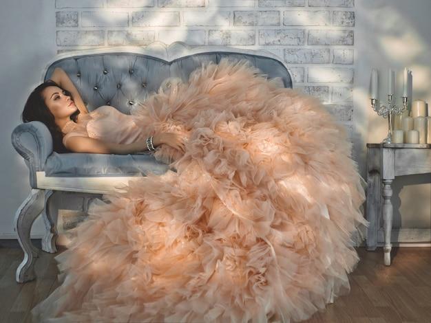 Piękna dama w pięknej modnej sukni na kanapie