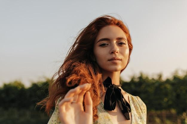 Piękna dama z lisimi falującymi włosami, uroczymi piegami i czarnym bandażem na szyi w letniej uroczej sukience patrzącej z przodu na zewnątrz