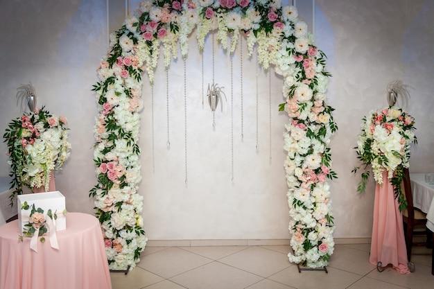Piękna dekoracja ślubna z bukietem róż w szklanym wazonie na stole.