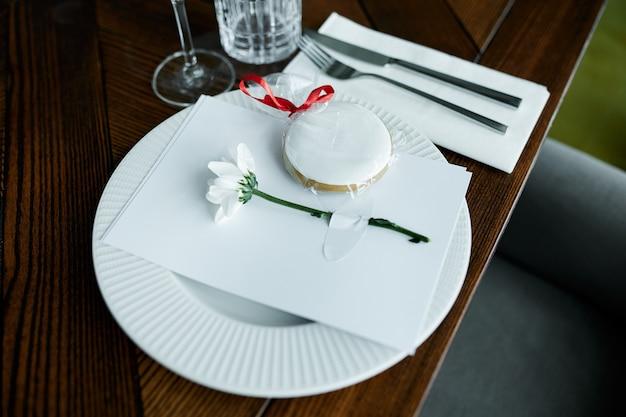 Piękna dekoracja świątecznego stołu z naczyniami i sztućcami, ozdobiona kwiatami i wstążkami. świąteczne nakrycie stołu.