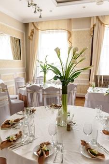 Piękna dekoracja święta weselnego z kwiatami i zielenią z dekoracją florystyczną. przygotowania do ślubu