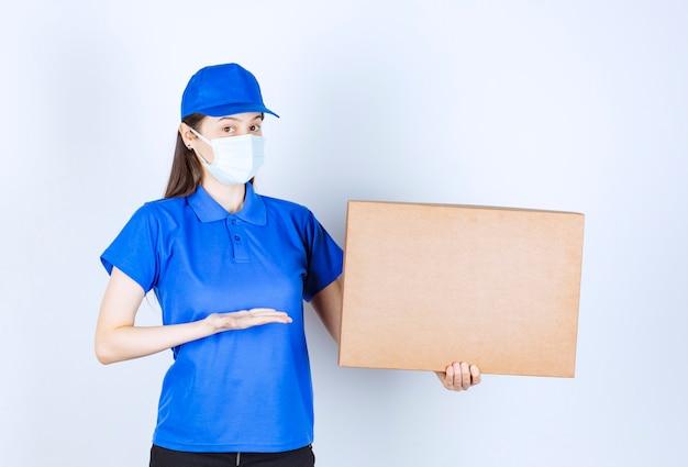 Piękna deliverywoman w masce medycznej, trzymając opakowanie kartonowe.