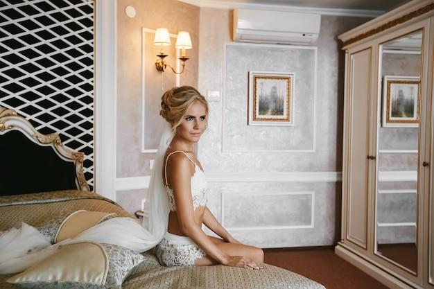 Piękna długonoga blondynka młoda kobieta o idealnym ciele w modnej białej koronkowej bieliźnie siedzi na łóżku w zabytkowym wnętrzu
