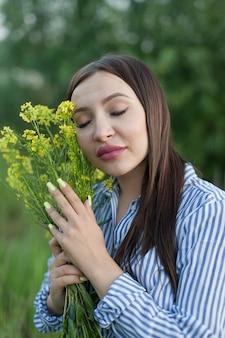 Piękna długowłosa brunetka na polu przytula bukiet żółtych kwiatów i zamyka oczy