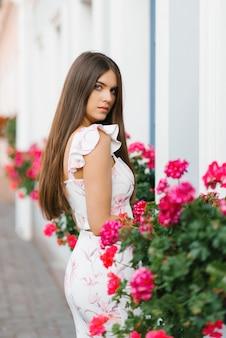 Piękna długowłosa dziewczyna stoi w otoczeniu różowych kwiatów latem w mieście.