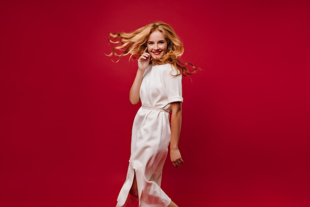 Piękna długowłosa dziewczyna tańczy z uśmiechem na czerwonej ścianie. błogi kaukaski dama w białej sukni, zabawy na imprezie.