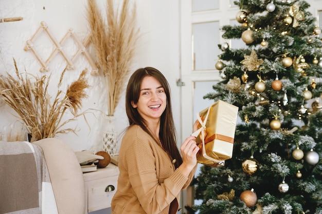 Piękna długowłosa dziewczyna w pobliżu choinki trzymając złote pudełko z prezentem i uśmiecha się do kamery