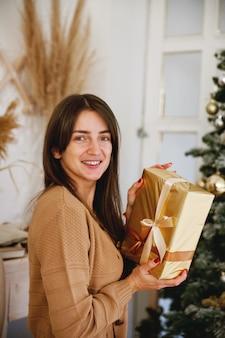 Piękna długowłosa dziewczyna w pobliżu choinki trzymając złoty prezent i uśmiecha się do kamery