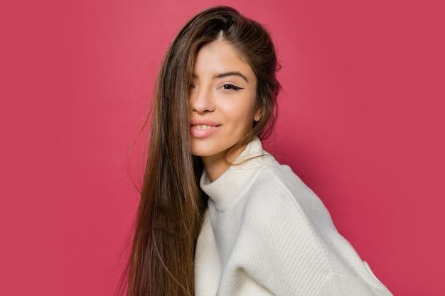 Piękna długowłosa kobieta w przytulnym białym swetrze i dżinsach pozujących na różowo.