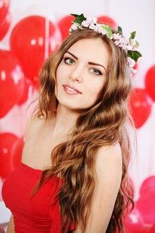 Piękna długowłosa kobieta z dużymi czerwonymi balonami