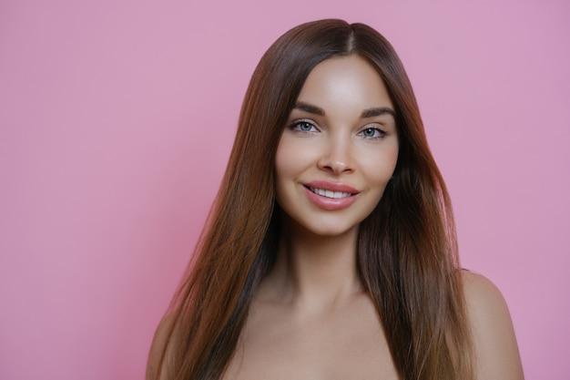 Piękna długowłosa kobieta z przyjemnym uśmiechem, ma idealną skórę
