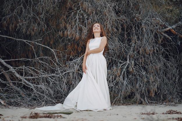 Piękna długowłosa panna młoda w wspaniałej białej sukni w naturze