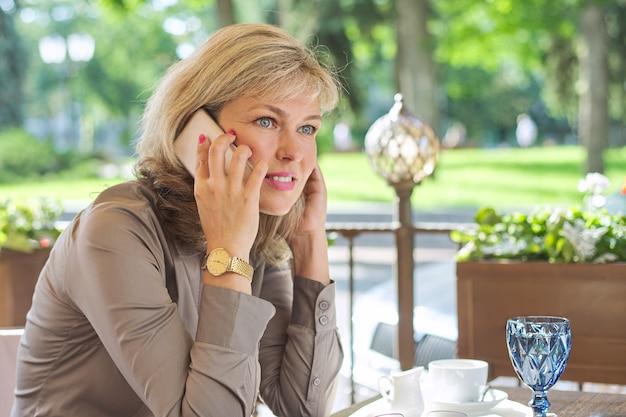 Piękna dojrzała blond kobieta rozmawia na smartfonie. uśmiechnięta biznesowa kobieta w średnim wieku pijąca kawę w kawiarni na świeżym powietrzu